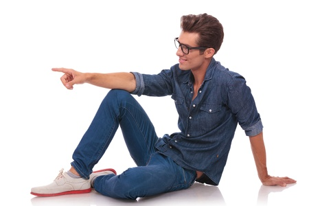 see side: side view of a casual young man sitting on the floor and pointing and looking to the side of the camera, while smiling  isolated on white