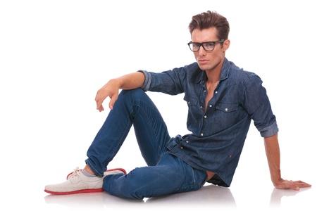 poses de modelos: pensativo joven ocasional está mirando con una mirada profunda a la cámara mientras que se sienta relajado en el suelo aislado en blanco Foto de archivo