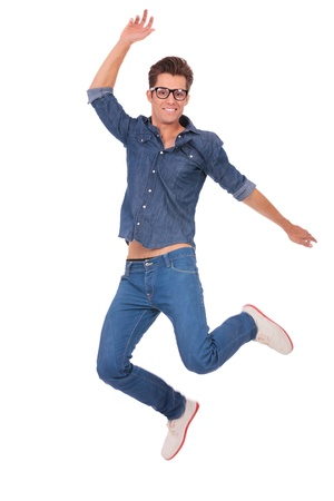air jump: casual man jumping and smiling to the camera, over white background