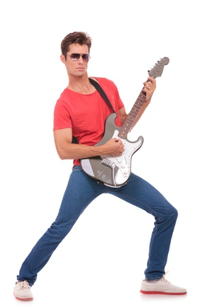 playing the guitar: casual young man playing his electric guitar and looking at the camera  isolated on a white background