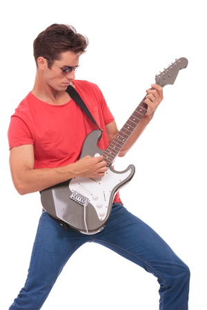 passionately: casual young man passionately playing on an electric guitar  isolated on a white background