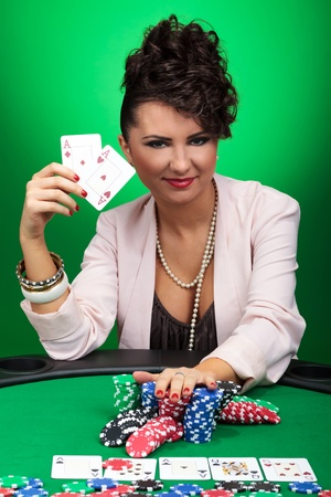 attractive young woman showing you her aces while going all in with a smile on her face  on green background photo