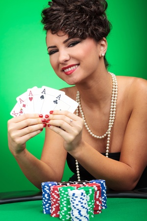 beautiful young woman showing you her four aces and king and smiling victorious  on green background photo