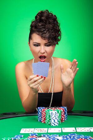 unbelievable: joven mujer sexy mirando sorprendido por su mano de p�quer incre�ble sobre fondo verde