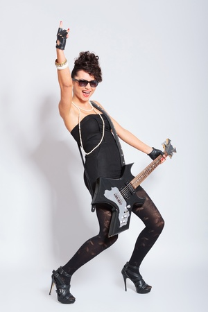 sexy young fashion woman rocking with an electric guiar, showing rock gesture and shouting  on light background photo