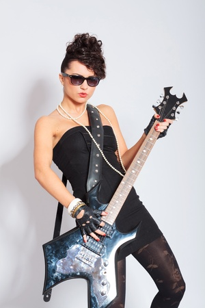 sexy young fashion woman playing an electric guitar and looking at the camera  on light background photo