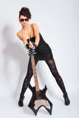 sexy young fashion woman holding both her hands on an electric guitar and looking fiercely at the camera  on light background photo