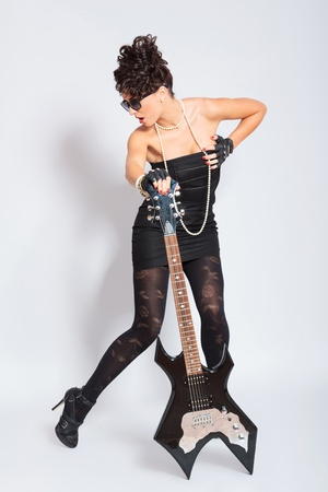 sexy young fashion woman posing with an electric guitar and looking away from the camera  on light background photo