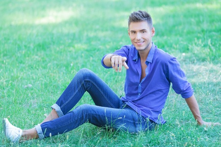 young casual man sitting in the park and pointing at the camera while smiling photo