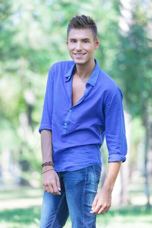 unbuttoned: young casual man posing outdoors with a smile on his face