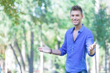 welcoming: young casual man welcoming you in the park with a big smile on his face