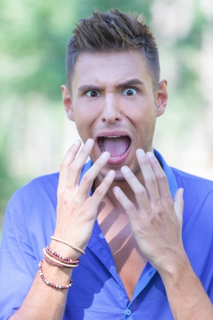 horrified: closeup portrait of a young casual man shouting out of horror in a park
