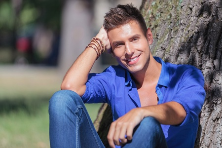 young casual man sitting next to a tree and smiling to the camera photo