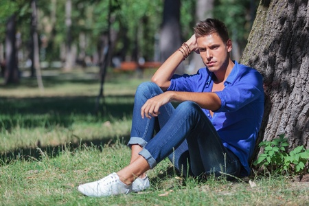 young casual man sitting on the ground and leaning to a tree trunk while looking down with a pensive expression photo