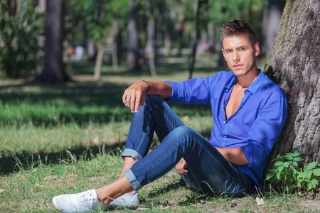 sitting on the ground: young casual man with a serious look sits at the base of a tree in the park and looks at the camera Stock Photo