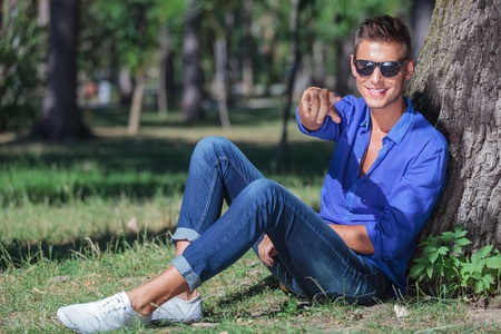sitting on the ground: young casual man sitting on the ground next to a tree and pointing at the camera while smiling