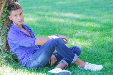 crossed legs: young casual man resting in the grass at the base of a tree with his legs crossed, looking at the camera with a serious look on his face