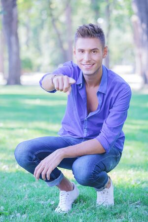 young casual man sitting crouched in the park and pointing and looking at the camera with a smile on his face photo