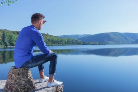 lejos: casual hombre joven sentado en un trozo de hormigón junto al lago y mirando en la distancia