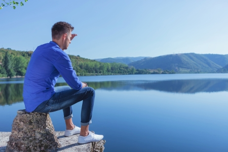 young casual man sitting on a concrete piece by the lake and looking away into the distance Stock Photo