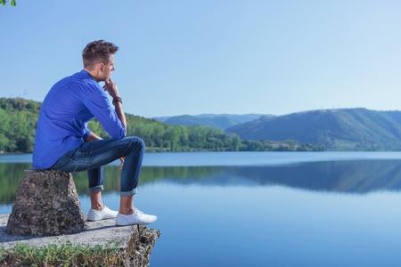 bloque de hormigon: casual hombre joven sentado en un pensativo en el borde de un estanque, en un bloque de hormig�n