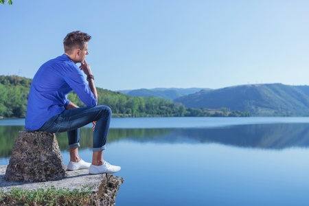 contemplative: young casual man sitting in a thoughtful on the edge of a pond, on a concrete block Stock Photo