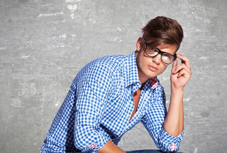 Fashion young man holding his fashionable glasses on gray background  Stock Photo - 18600638