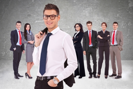 businessteam: successful business team, focus on man with coat on shoulder