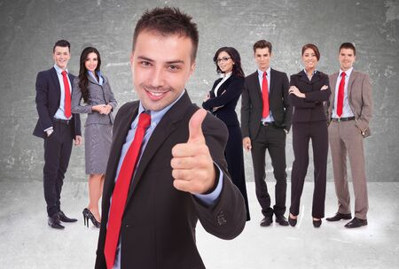 businessteamwork: young business man leader of a successful team making the thumbs up ok gesture