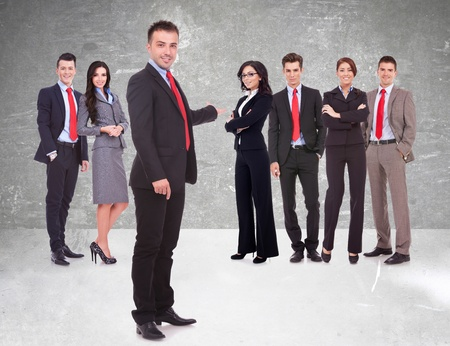 chairman: Successful happy business team being presented by a young leader, on gray background