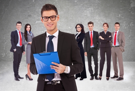 take a note: Leader holding a clipboard with business team behind Stock Photo