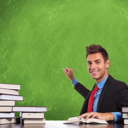 sketch book: business man sitting at desk and preparing to write concepts on a blank board , with a smile on his face Stock Photo