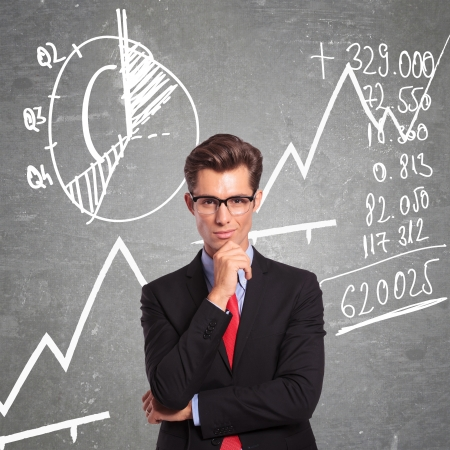 rapport: young business man standing in front of some graphs and charts with a pensive look on his face