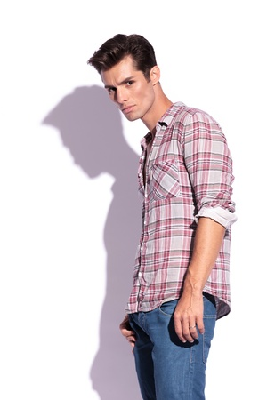 suspiciously: side view of a casual young man looking at the camera suspiciously. isolated on white background Stock Photo