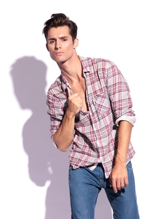 passionately: casual young man holding his hand on his unbuttoned shirt and looking passionately at the camera. isolated on white background