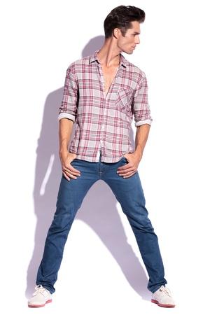 beine spreizen: Casual junger Mann, der mit seinen gespreizten Beinen und Daumen in den Hosentaschen, sich auf seine Seite, weg von der Kamera