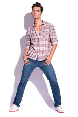 spread legs: portrait of a young casual man posing with thumbs in pockets and legs spread, looking at the camera. on white Stock Photo