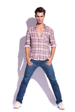 beine spreizen: schwere casual young Modell stehend mit den Daumen in den Taschen und mit gespreizten Beinen in die Kamera schauen. isoliert auf weiß, mit Schatten