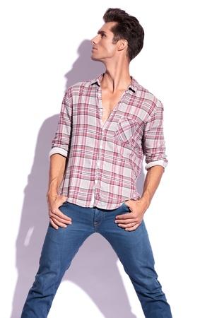 legs spread: casual giovane uomo che tiene i pollici in tasca con le gambe diffusione e alzando lo sguardo e ad un lato, lontano dalla fotocamera. isolato su sfondo bianco