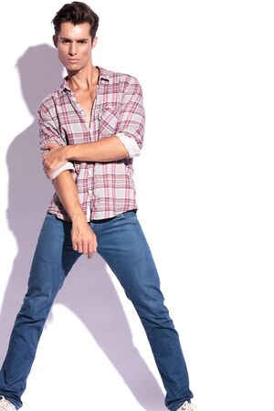 legs spread: casual giovane uomo che tiene il gomito con l'altra mano e le gambe si diffuse, mentre guardando la telecamera. isolato su sfondo bianco