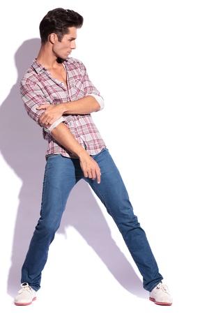 legs spread: joven casual con las piernas abiertas es la celebraci�n de su codo mientras mira a la c�mara. en blanco