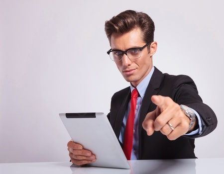 young business man sitting at the desk and pointing at the camera while holding a tablet in his other hand and looking at the camera photo
