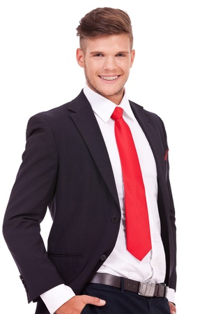 cutout picture of a young business man standing with his hands in his pockets and smiling to the camera. isolated on white background photo