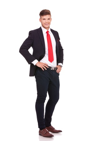 hands on waist: full length picture of a young business man standing with his hands on his waist and smiling to the camera. isolated on white background Stock Photo