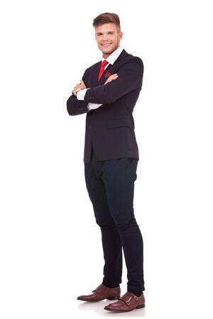 mani incrociate: quadro completo leght di un giovane uomo d'affari in piedi con le mani incrociate e sorridere alla telecamera. isolato su sfondo bianco