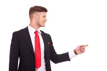 sideway: young business man pointing and looking to his side with a smile on his face. isolated on white background