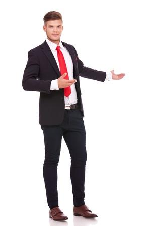 invitando: foto de cuerpo entero de un joven hombre de negocios que invita al fondo, la presentación que el camino con una sonrisa en su rostro. aislado en fondo blanco Foto de archivo