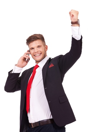 young business man hearing some good news on the phone and cheering with a big smile on his face. isolated on white background photo