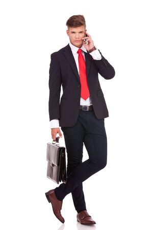 man legs: full length picture of a young business man standing with his legs crossed and holding a briefcase while speaking at the phone and looking at the camera with a serious look on his face. isolated on white background Stock Photo