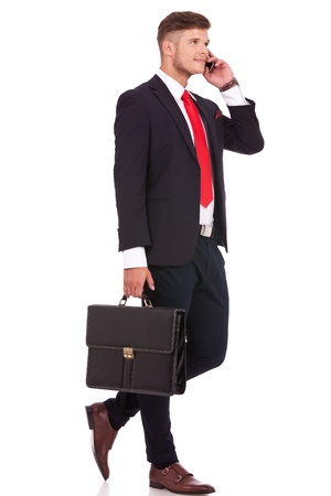 full length picture of a young business man walking with his briefcase and talking on the phone while looking away from the camera. isolated on white background photo